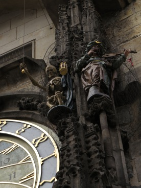 Animated Death and human statues to the side of the clock